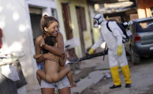 Una mujer brasileña se aleja con su hijo en brazos del operario que rocía insecticida contra el mosquito 'aedes aegypti' en una calle de Recife.