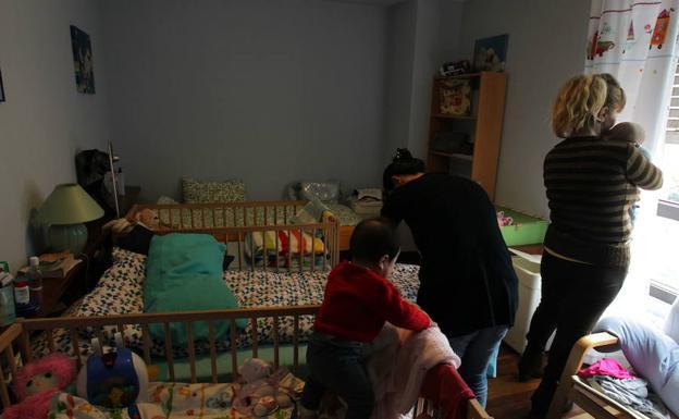 Varias mujeres atienden a sus hijos en un piso de acogida.